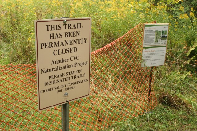 A trail closure sign and orange fencing mark the entrance to site.