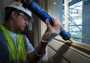 Man applying caulking to a window - Image courtesy of USCapitol via Wikimedia Commons