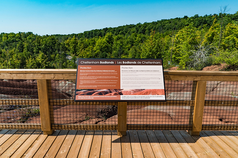 Interpretive signage affixed to the railing on a viewing platform, overlooking the Badlands.