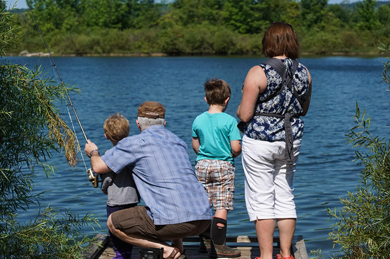 A family of two adults and two children look out across the water while fishing.