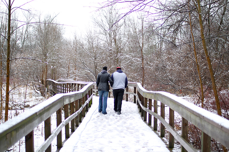 Two people walk together along the boardwalk in winter.