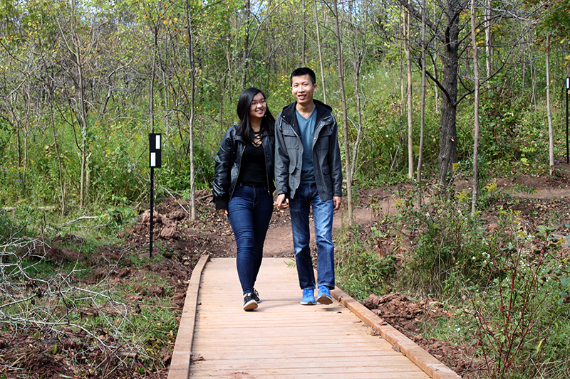 Two people walk together along a boardwalk on a trail.