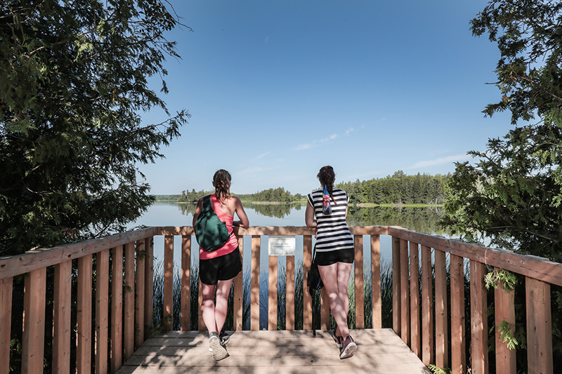 Two park visitors with backpacks stop at a lookout point along the trail at Island Lake to look across the water.