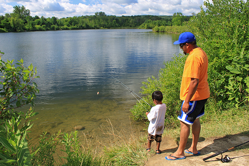 An adult and small child stand at the water's edge together while the child holds a fishing rod.