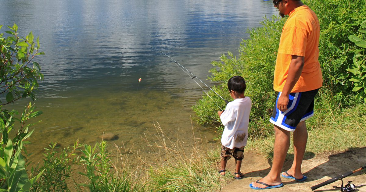 Parent and child fishing at the end of a pond