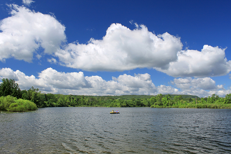 A boat in the middle of the lake, under a large sky of blue with fluffy white clouds.
