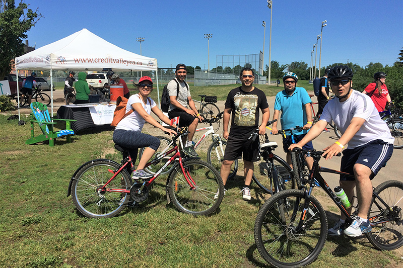 Adults pose for photo with their bikes
