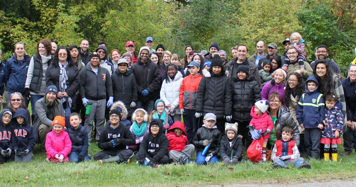 Group of staff, adults and children posing together outdoors at a Fletchers Creek SNAP event.