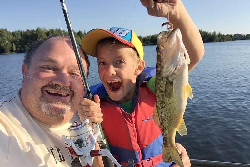 A young boy with an adult, holding up a large bass at Island Lake.