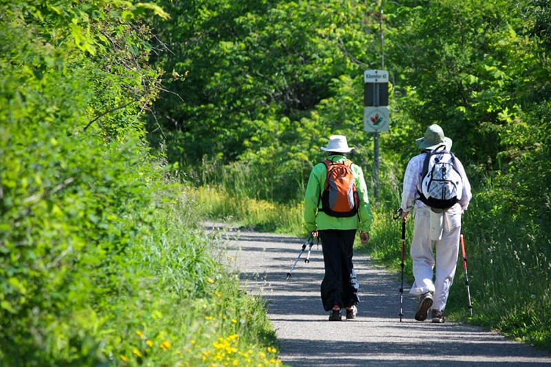 Two hikers with backpacks walk the trail along the Elora Cataract Trailway.