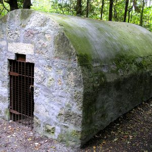 A limehouse powder house with a rounded roof and doorway on one end.