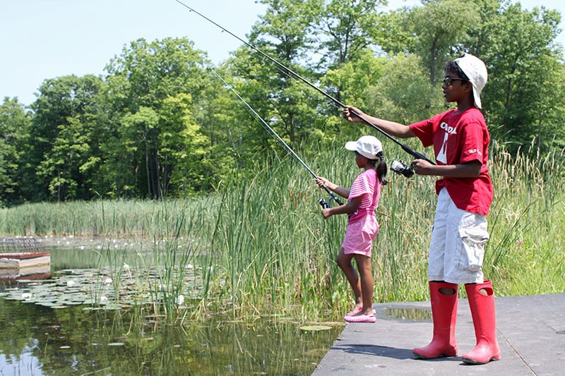 Two young children fishing on a fishing pier by a lake