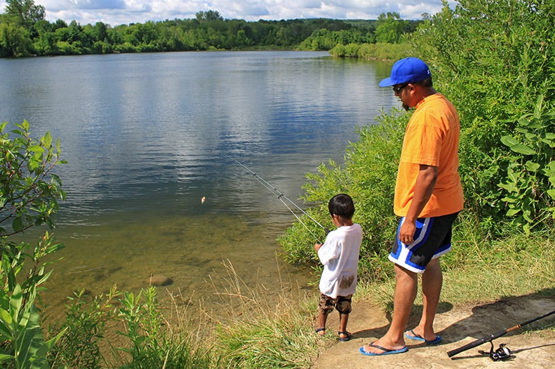 A man and his young son standing together at the edge of the water at Ken Whillans, fishing.