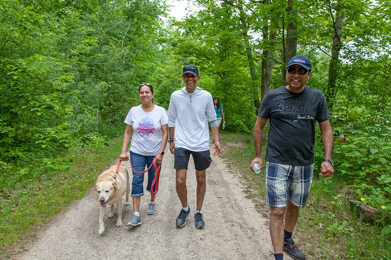 A group of adults walking a dog along a trail at Terra Cotta Conservation Area.
