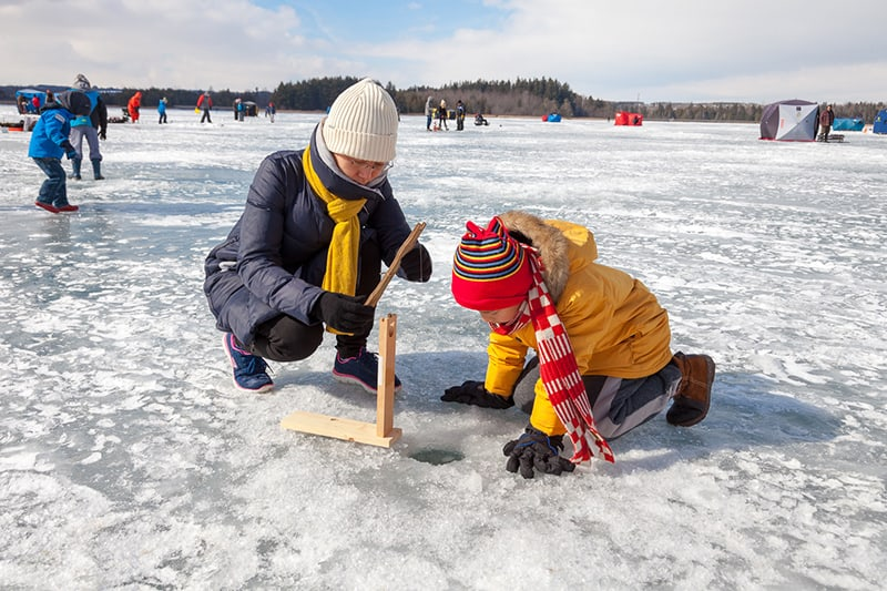 A woman and child ice fishing at Island Lake Conservation Area.