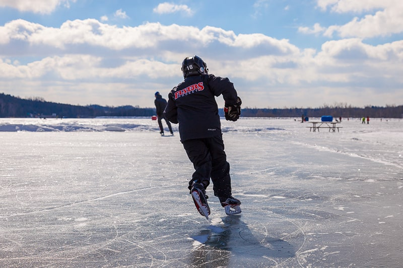 A person wearing a hockey helmet and hockey skates crosses a rink on the frozen Island Lake.