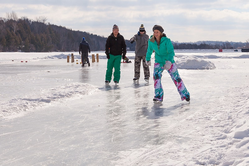 A group of three friends skating on the open ice at Island Lake Conservation Area with trees in the background