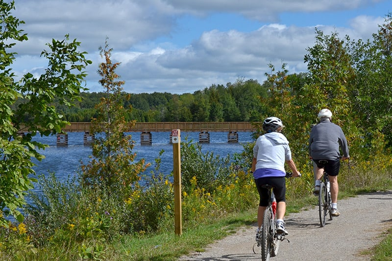 Two park visitors ride their bikes along the trail at Island Lake, passing the water and heading towards a bridge.