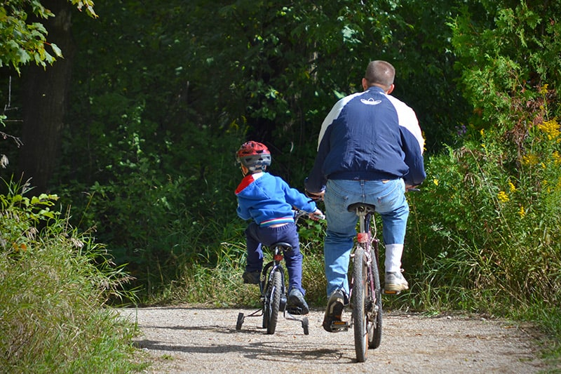 An adult rides his bike with a child on a tricycle along a path at Island Lake Conservation Area.