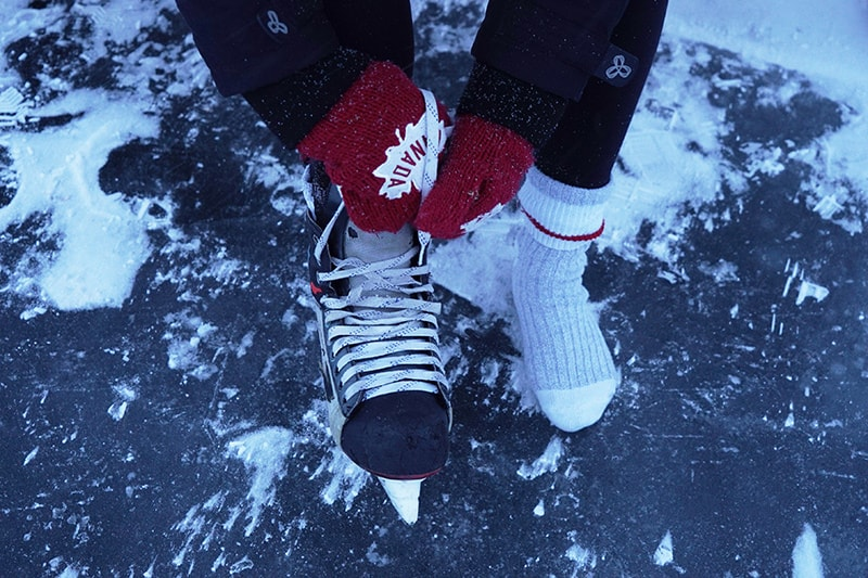 A park visitor putting on their ice skates over thick woolen socks.