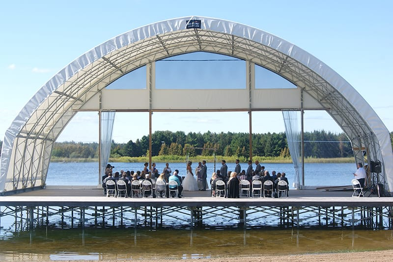 A group of people seated for a wedding on a water amphitheatre with the bride and groom standing at an archway and a lake and trees in the background