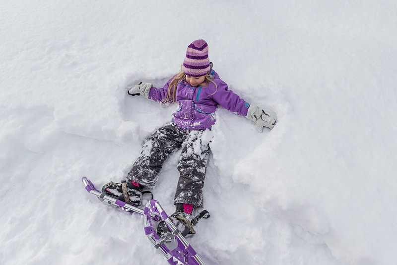 A young child makes snow angels in the snow while wearing snowshoes.