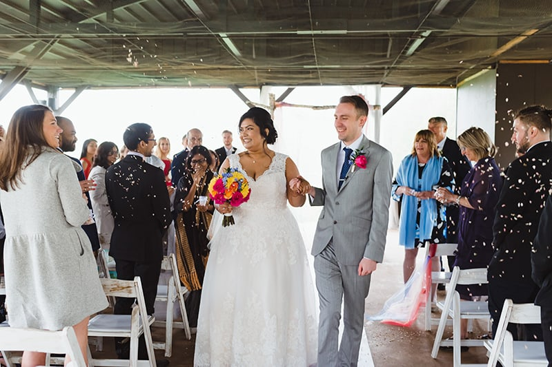 a bride and groom holding hands walking down the aisle of an outdoor pavilion with guests in the background