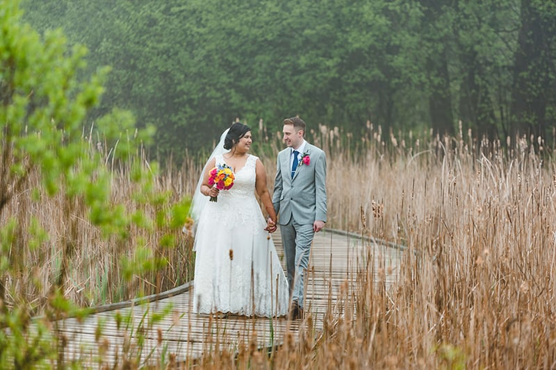 a bride and groom holding hands walking down a wetland boardwalk with trees in the background