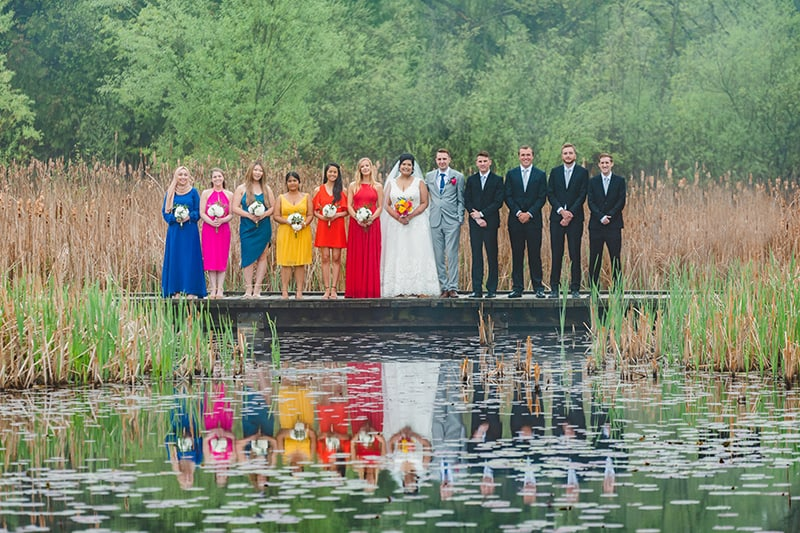 A wedding party lined up on a wetland boardwalk for wedding photos with trees in the background