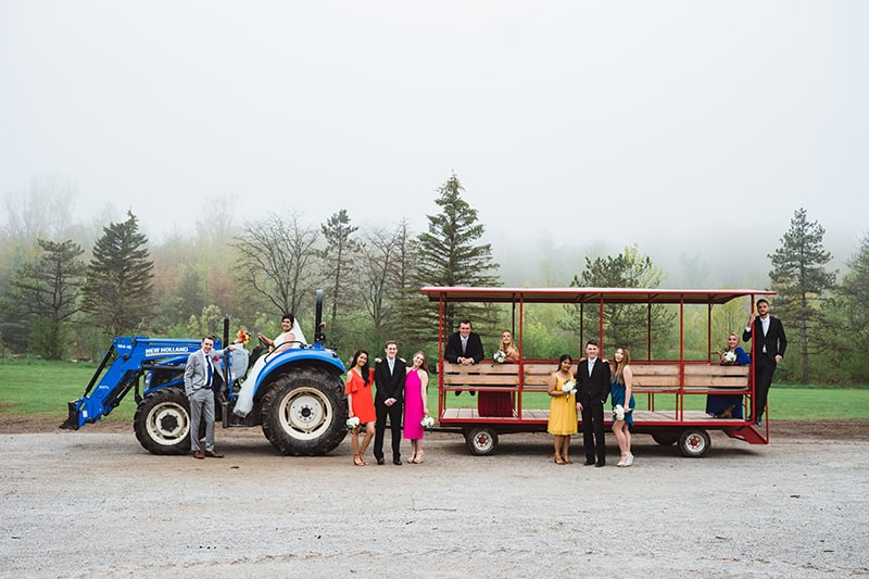 a couple and their wedding party standing in front of a tractor and wagon posing for wedding photos