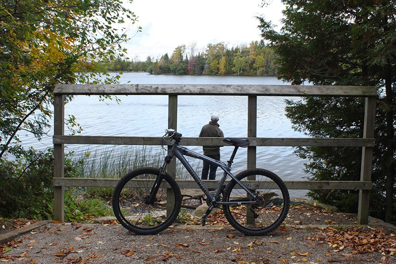 A visitor parks his bike on the side of the trail so that he can stand by the side of the lake at Island Lake Conservation Area.