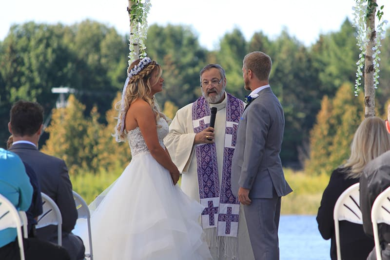 a couple standing with a officiant at their wedding on a water amphitheatre with the lake and trees in the background