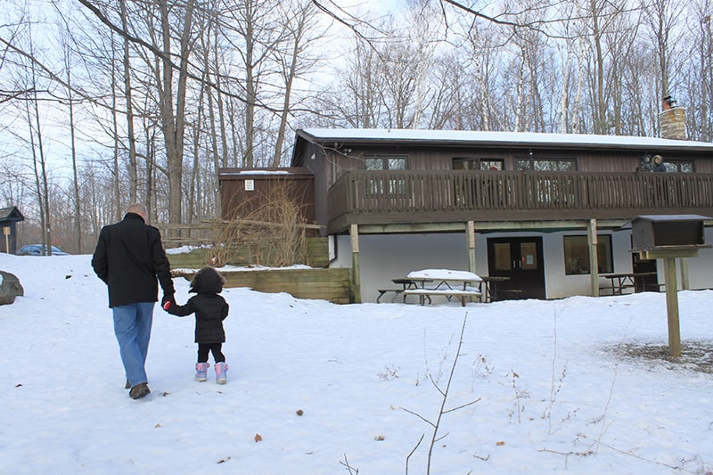 An adult and child walking through the snow behind the Outdoor Education Centre.