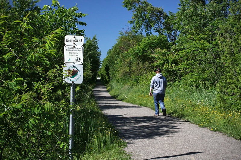 A person walks along a trail, past a sign for the Trans Canada Trail and a kilometre marking of 45 km.