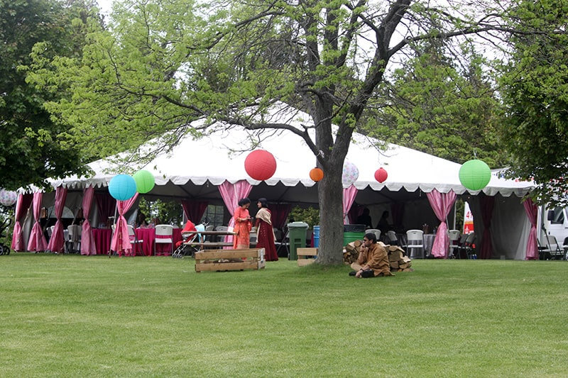 A large outdoor canopy tent set up for a wedding with decorations and colourful ornaments hanging from a tree in front of the tent. There are two people standing in front of the tent and one sitting by the tree.