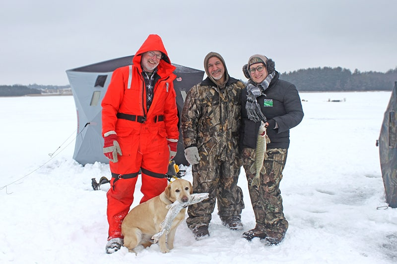 Three adults and a dog posing outside an ice fishing hut, showing off their catches.
