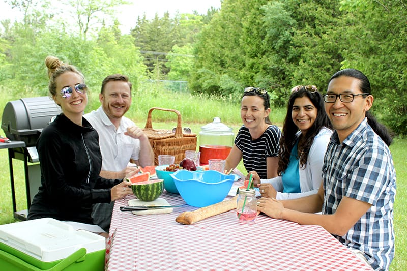 A group of friends pose smiling for the camera at a picnic in the park.