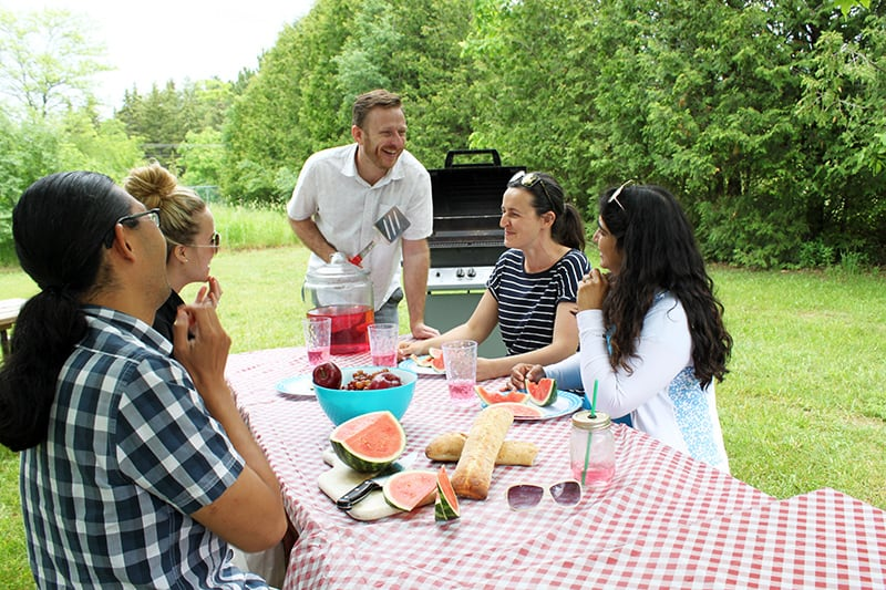 A group of friends enjoys a picnic together at a picnic table in the park.