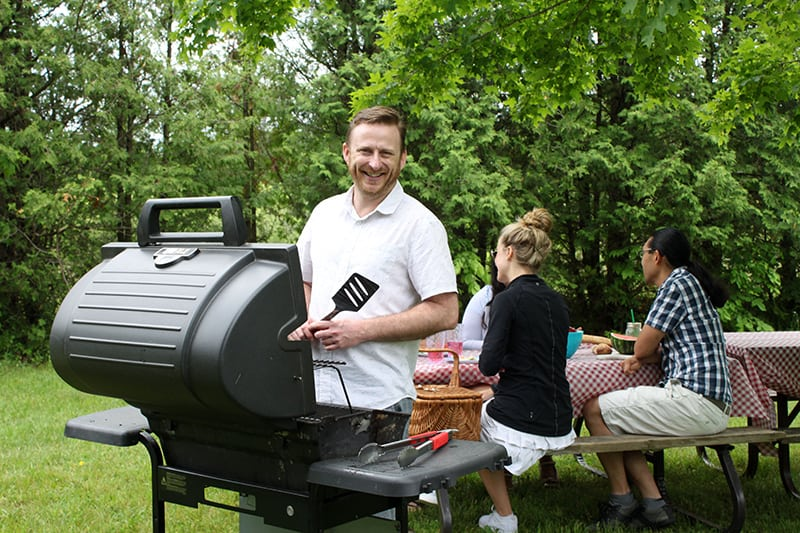 A man barbecues food for his friends at a picnic in the park.