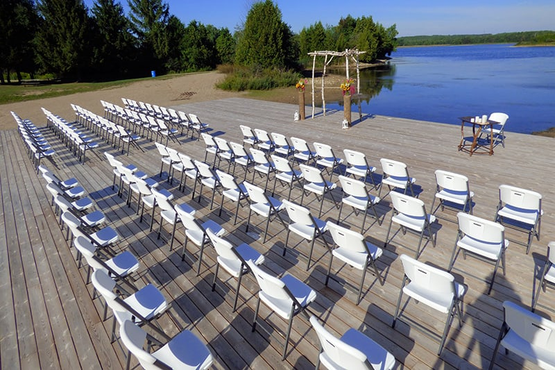 an outdoor stage with aisles of chairs and an archway set up for a wedding with a lake and trees in the background