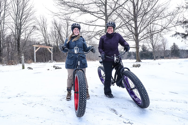 Two fat tire bike riders pause to smile for the camera.