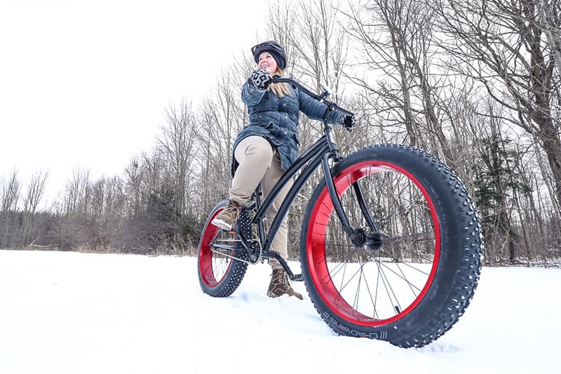 A park visitor on a fat tire bike in the snow at Island Lake Conservation Area.