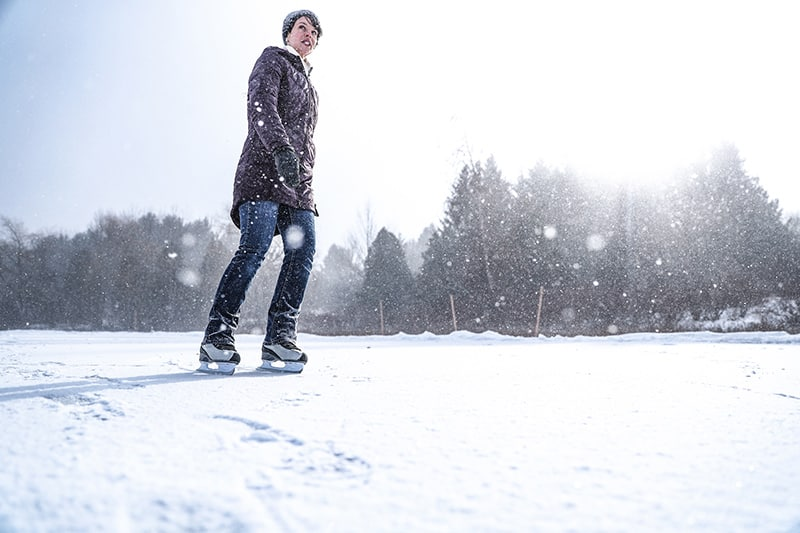A person skating on the frozen lake at Island Lake while snow is falling and trees in the background