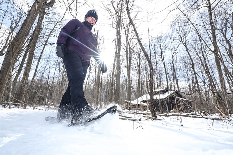 A park visitor snowshoes past a building at Island Lake Conservation Area.