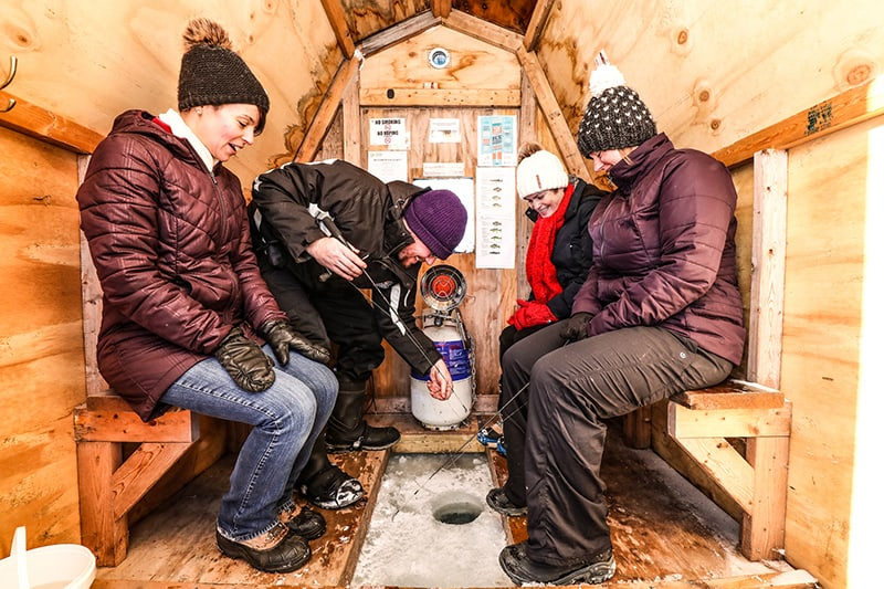 Four friends sitting in a rented ice fishing hut, fishing at Island Lake Conservation Area.