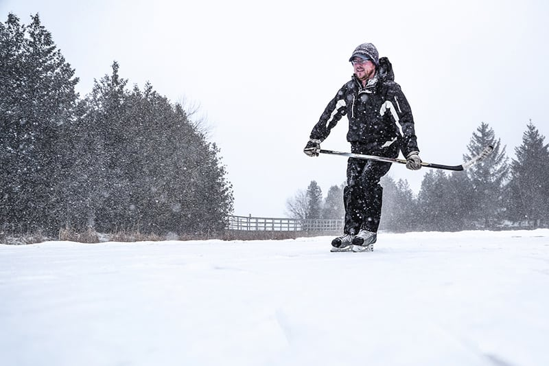 A hockey player skating at Island Lake Conservation Area with trees and a foot bridge in the background