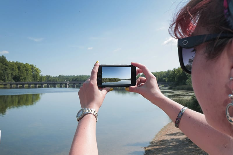 A park visitor takes a photo on their phone of the lake at Island Lake Conservation Area.