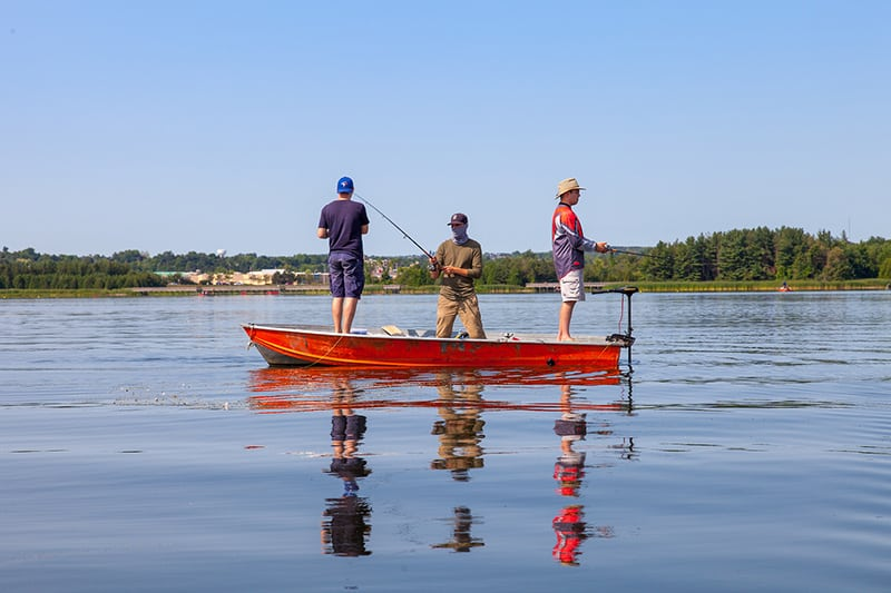Three men standing on a boat in the middle of the lake, fishing. The sky is blue and the water is still.