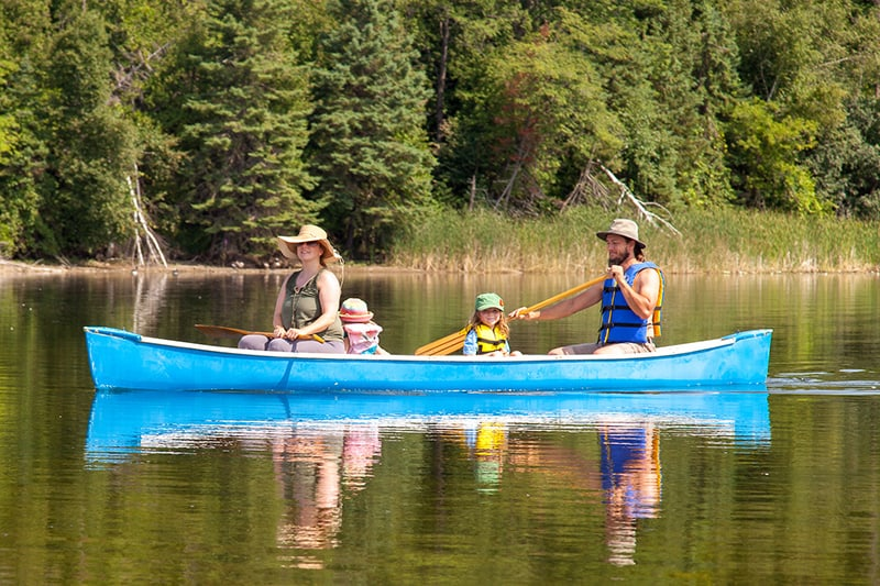 A family with two parents and two small children in a canoe at Island Lake Conservation Area, paddling on still waters.