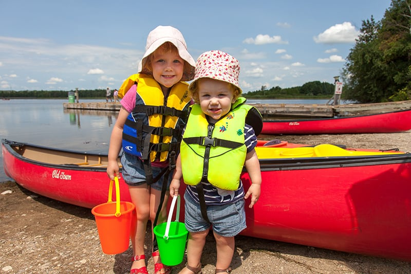 Two little children wearing life vests and sun hats, standing in front of canoes on the beach at Island Lake, holding plastic buckets.